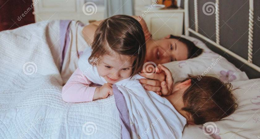 Little Girl Playing Over Boy Lying Bed